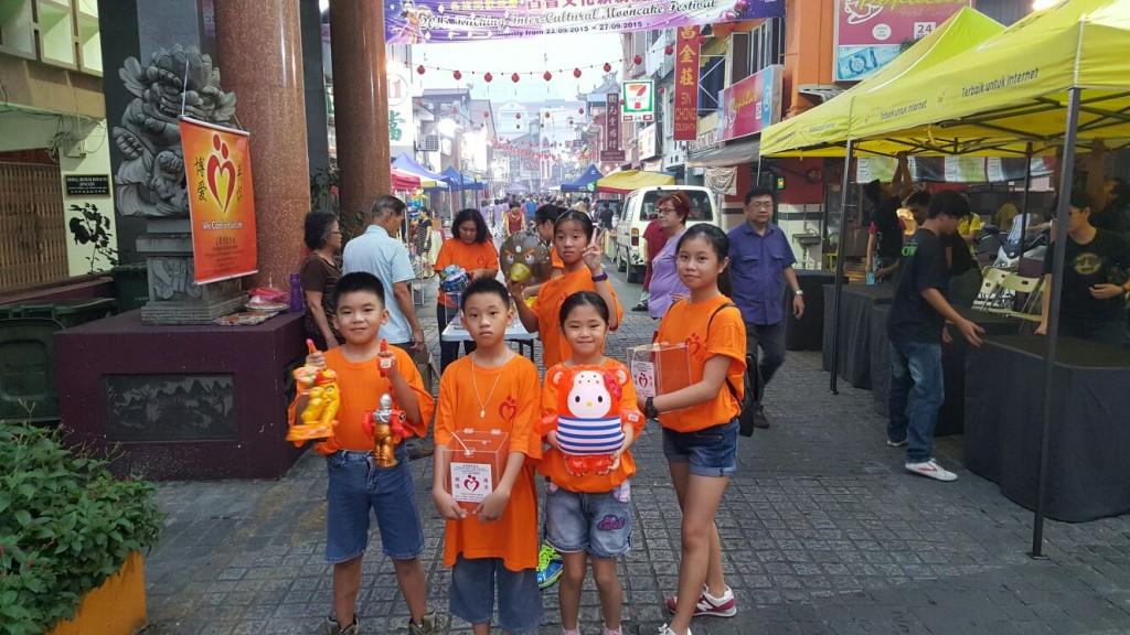一班博爱小志工趁着学校假期,到古晋文化缤纷庆中秋摊位,帮晋博协理事派灯笼,也为病人募捐。